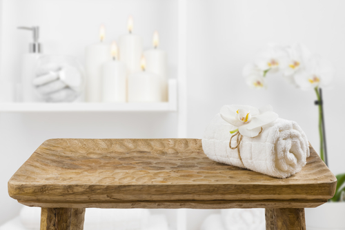 towel rolled up with flower on wooden bench